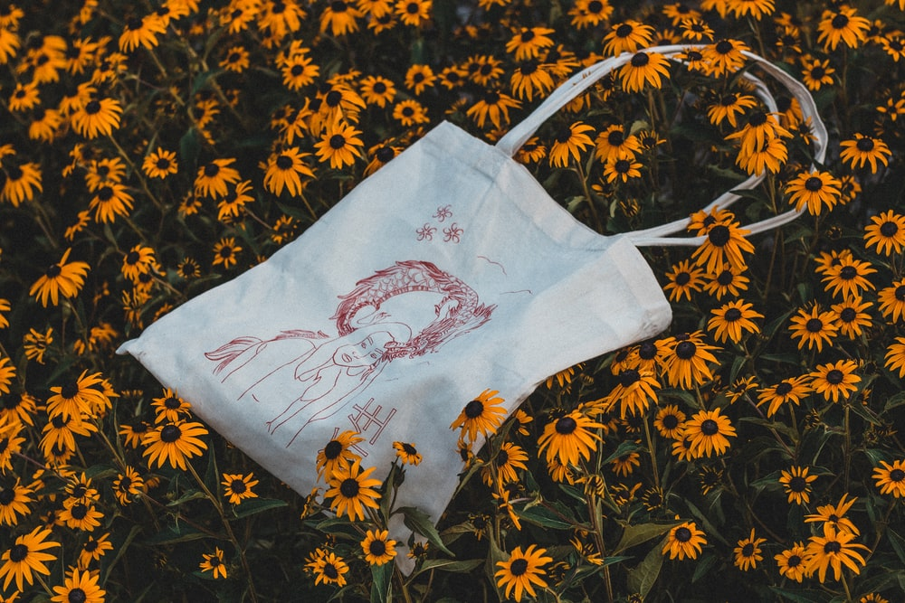 white and brown handbag on bed of sunflowers