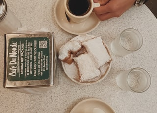 black coffee in white ceramic mug near sliced cake, water in drinking glass, and clear condiment shaker on table