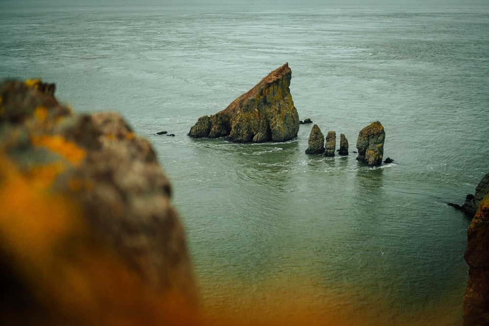 bird's eye photography of rock formation on body of water