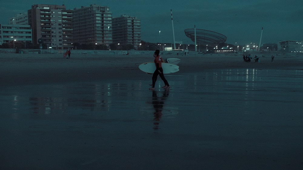 person walking on seashore holding surfboard at night