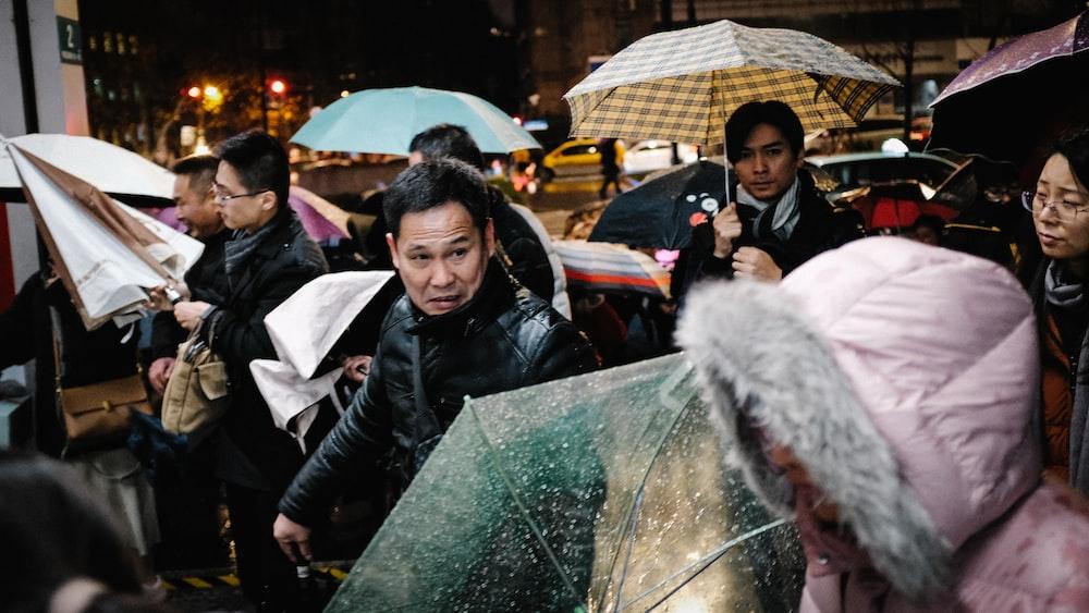 crowd holding umbrellas during daytime
