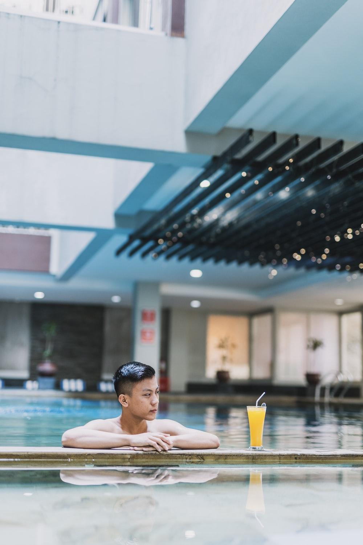 man in pool near mango juice during daytime