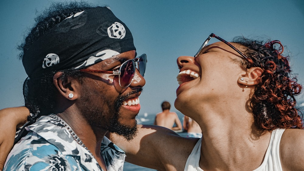 close-up photography of smiling man and woman near outdoor during daytime