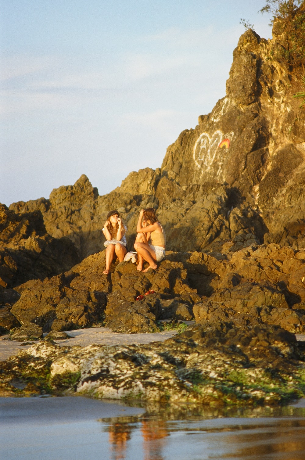 man and woman sitting on stone near sea during daytime