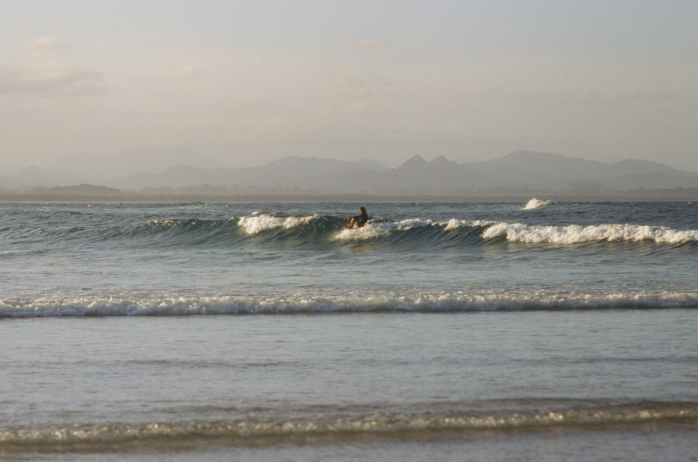 person on sea waves during daytime