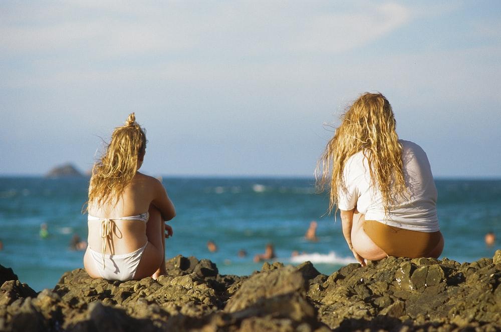 two women sitting on rock beside seashore during daytime