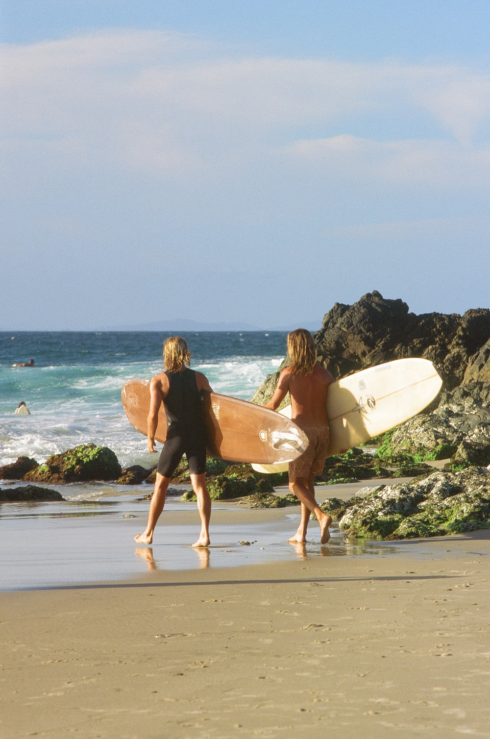 man and woman holding surfboard