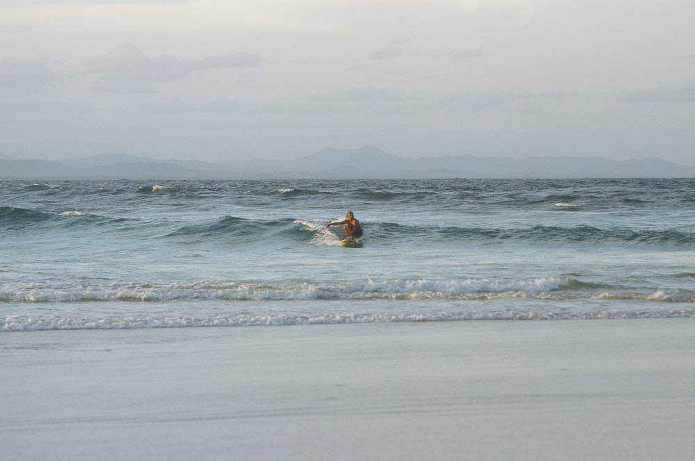 photography of person doing surfing during daytime