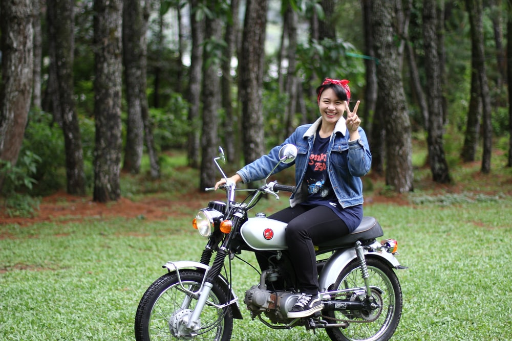 woman riding motorcycle in forest