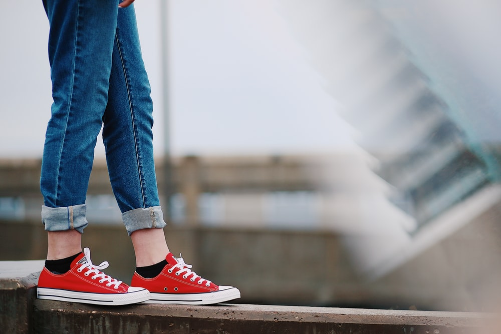 person in red Converse All-Star low-top sneakers standing on fence