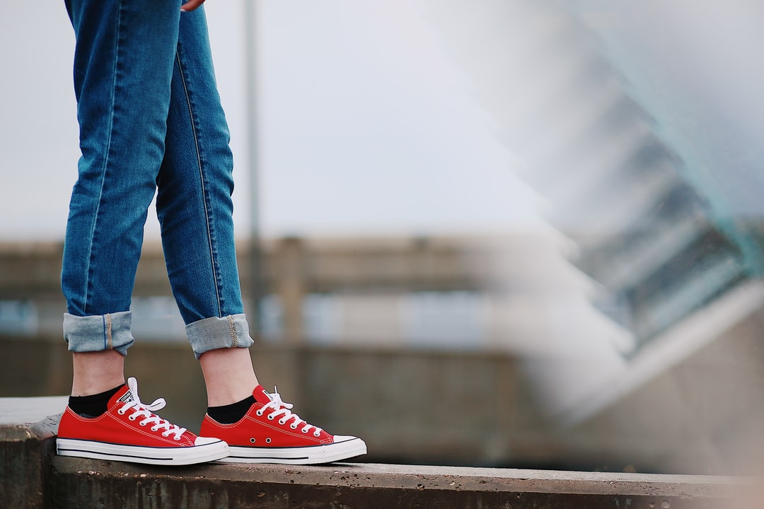 girl's legs wearing red converse walking