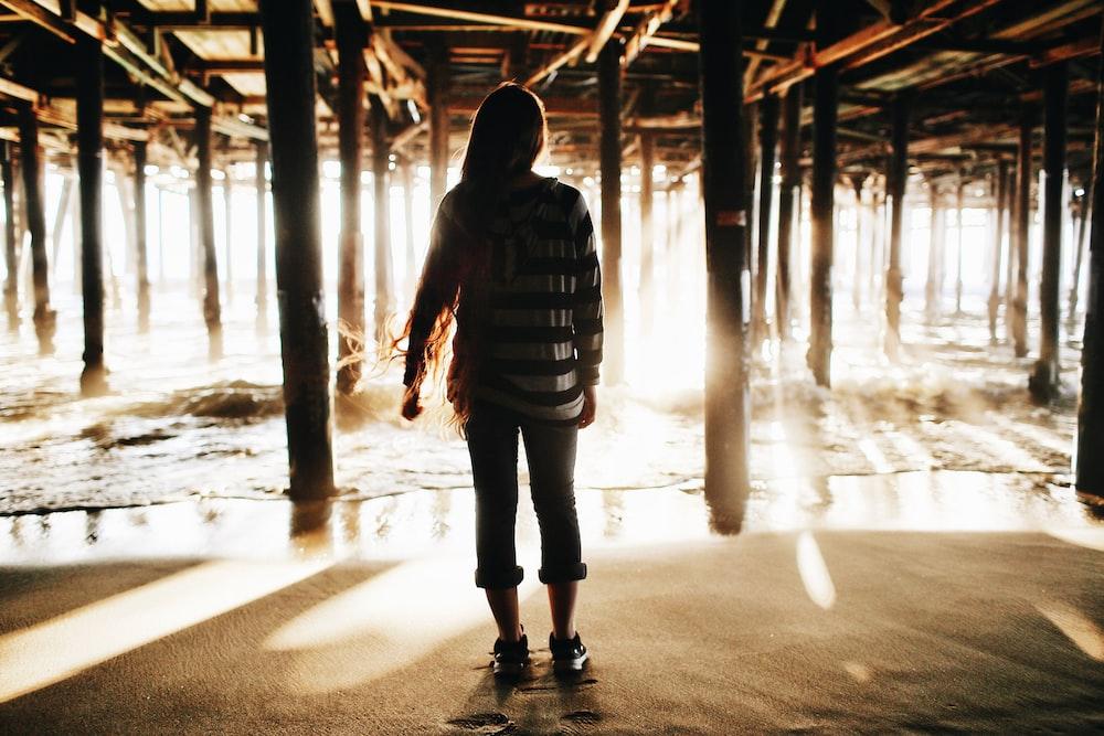woman standing in sand under wooden dock near sea