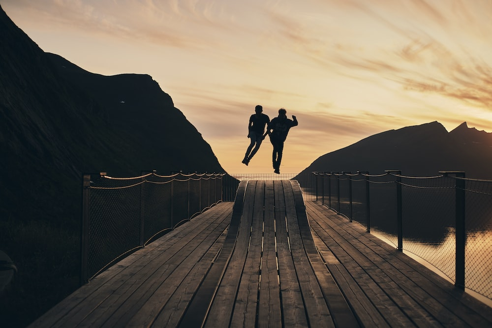silhouette view of couple jump on wooden hump beside body of water