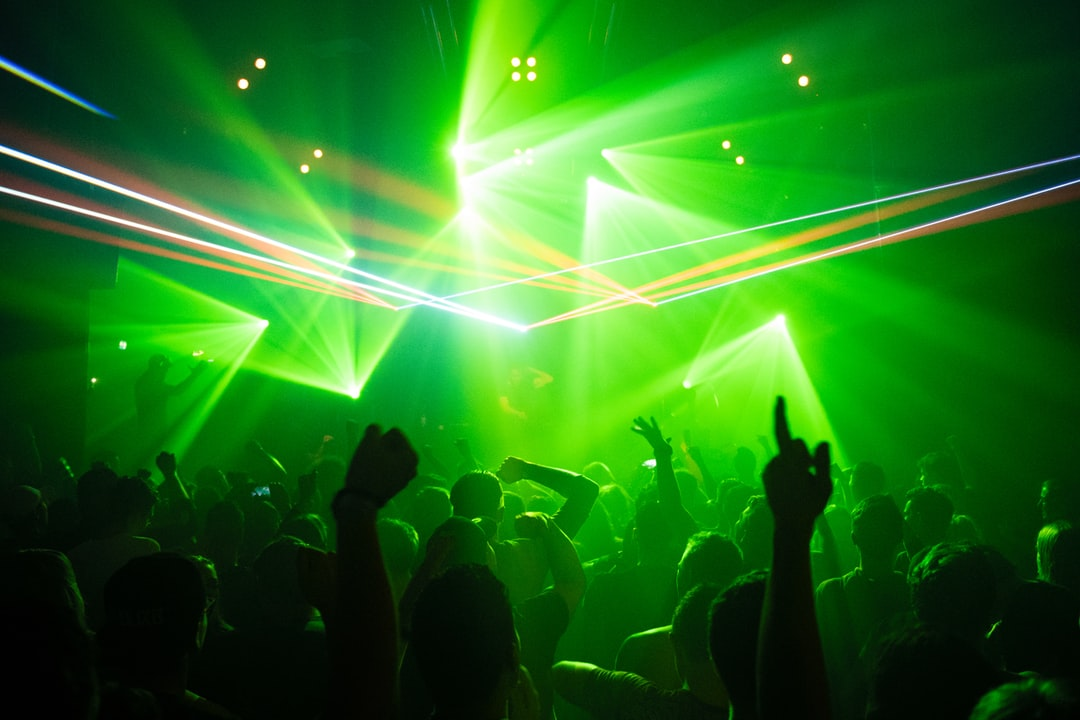 People dancing in a club while a DJ is playing electronic music with lasers