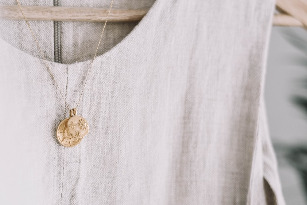 gold-colored pendant necklace on hanged dress