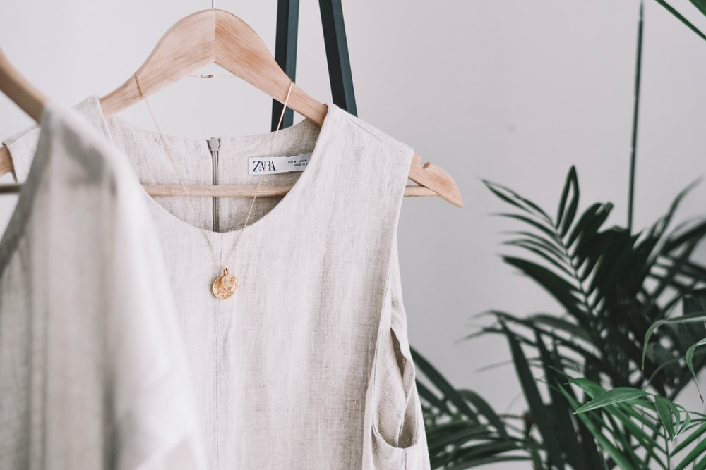 white crew-neck sleeveless top with gold-colored necklace