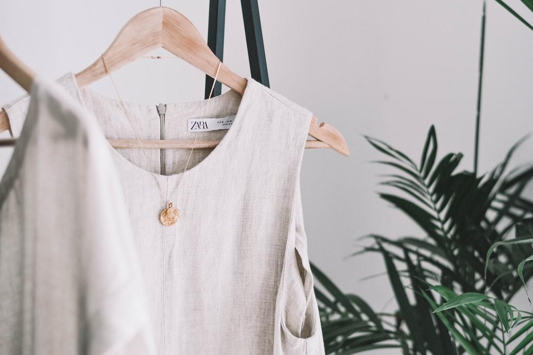Beige Linen Dress Hanging In Bedroom Interior - unsplash