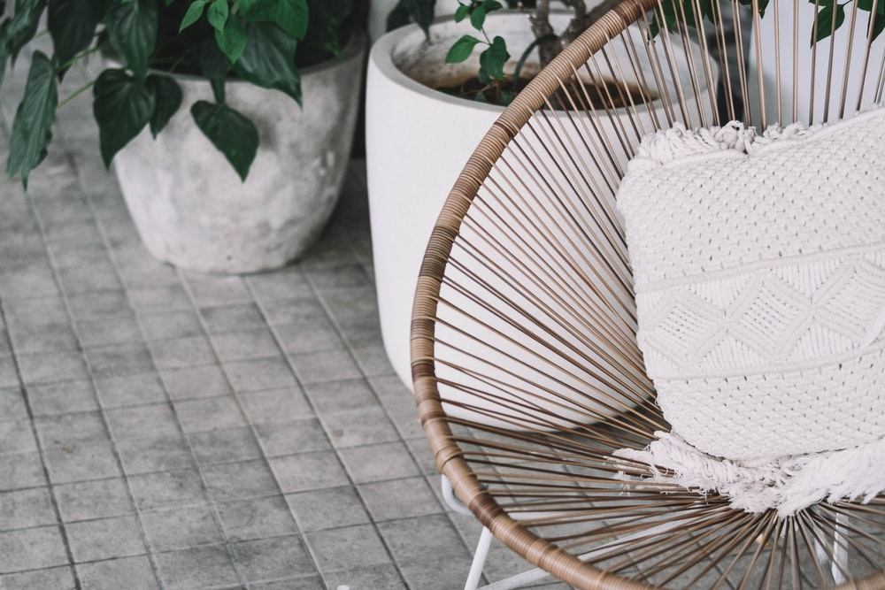 white pillow on brown chair beside plants