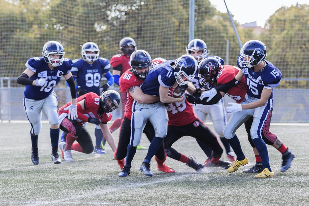 two teams playing football during daytime