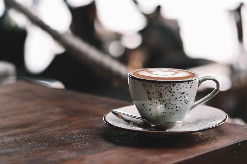 selective focus photography of full white ceramic mug on saucer on brown wooden table