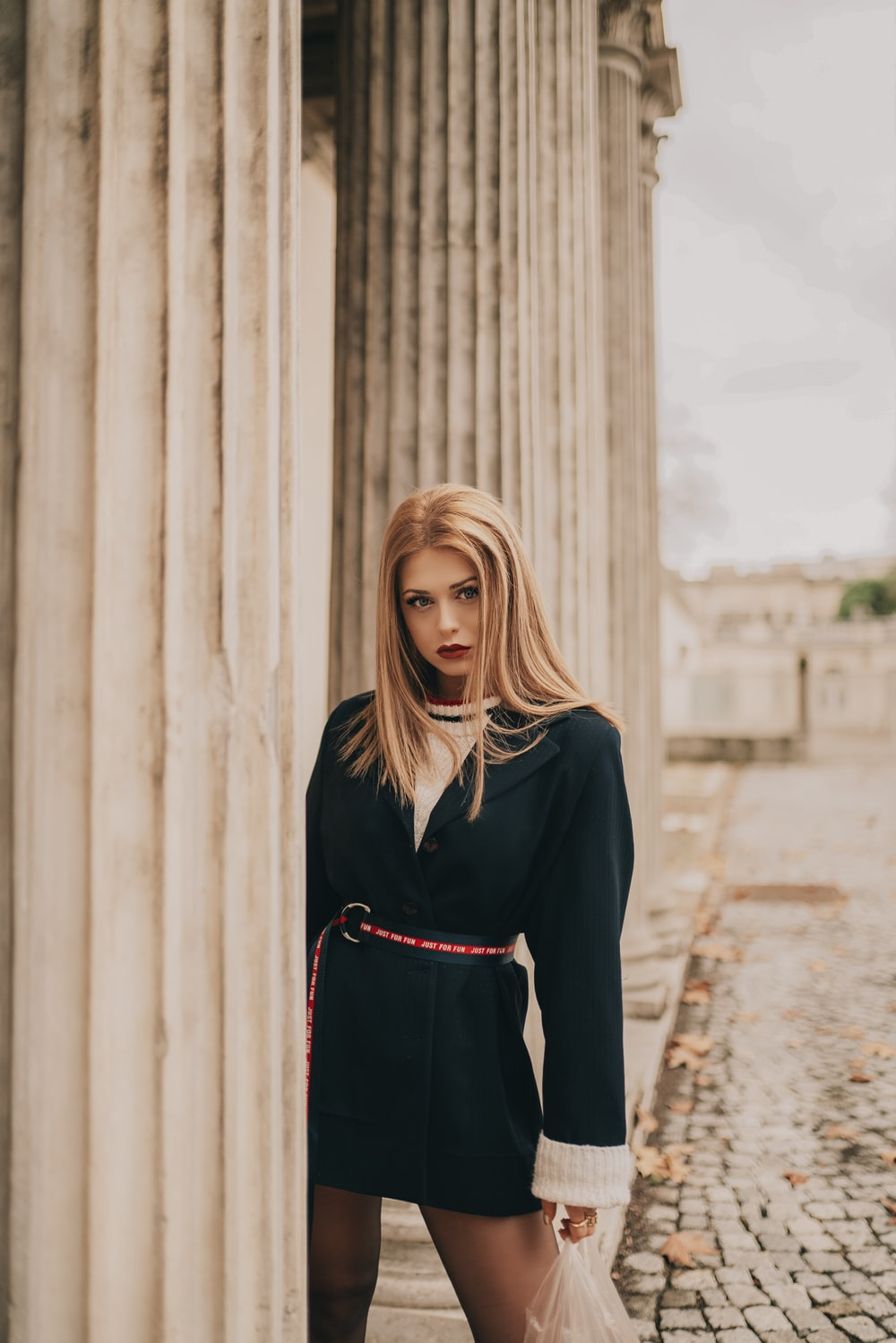 selective focus photography of woman wearing black long-sleeved dress during daytime