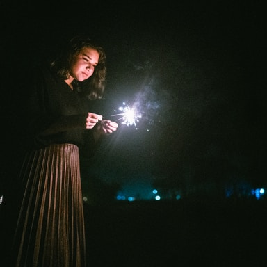 standing woman holding two sparklers
