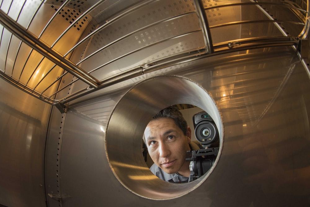 man peeking on hole with DSLR camera