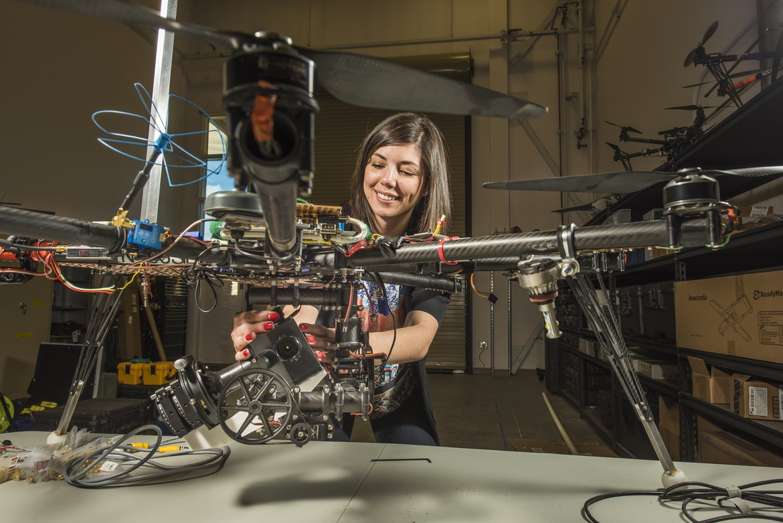 woman repairing drone inside room