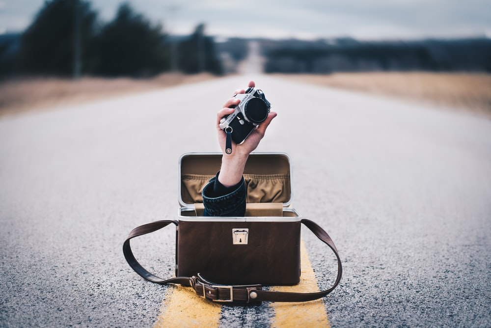 black and gray camera and bag on road