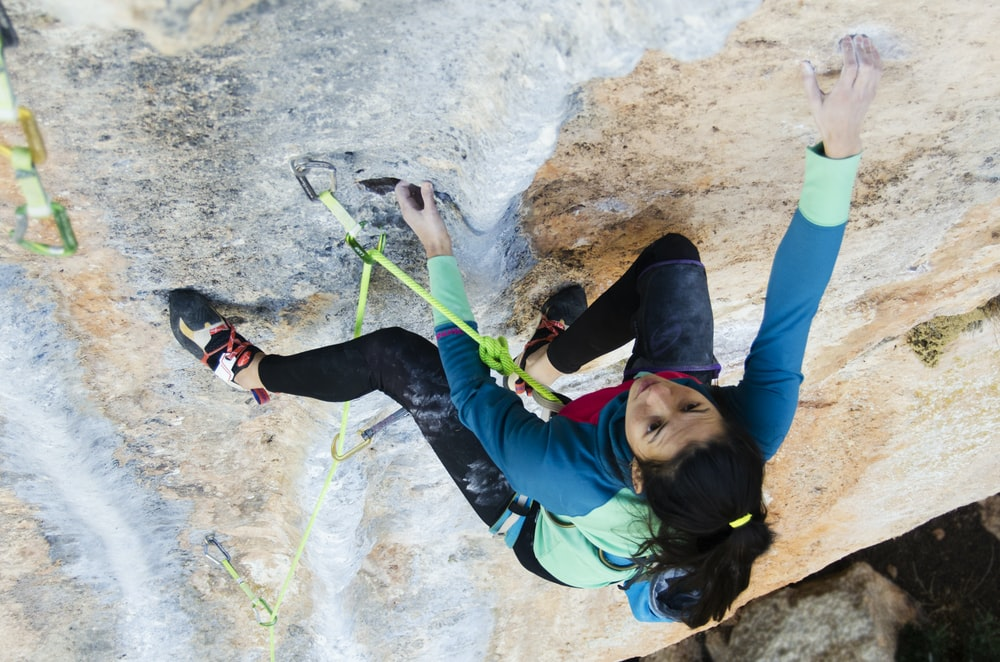 woman climbing rock formation