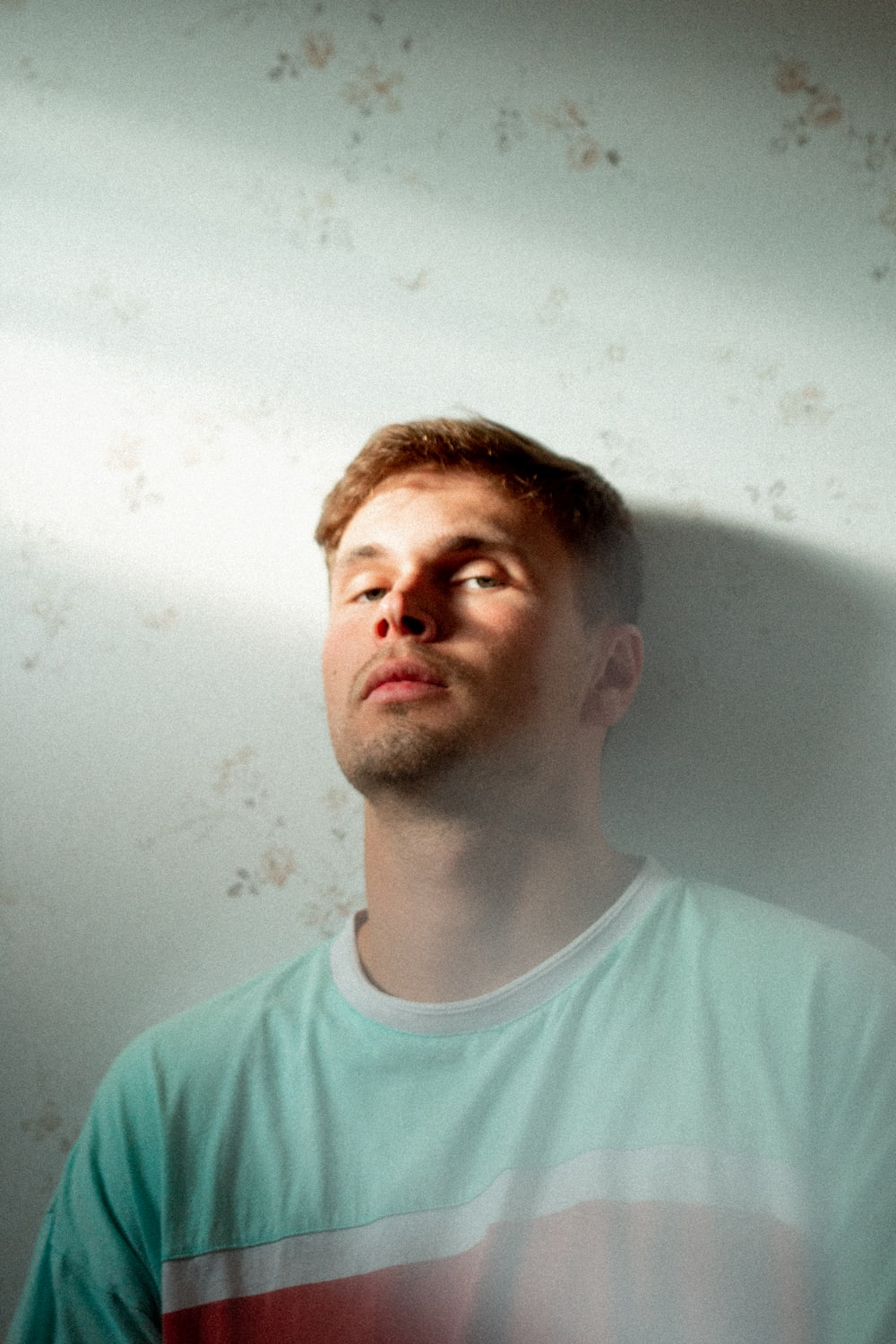 man leaning on white painted wall