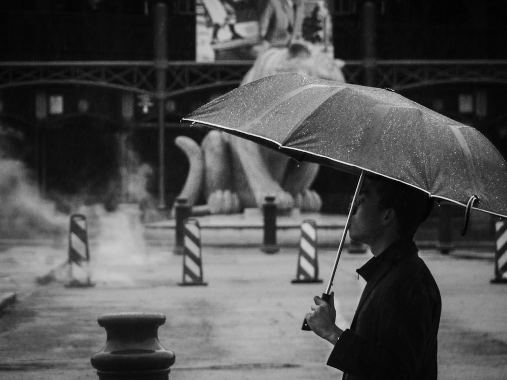 grayscale photo of man holding umbrella