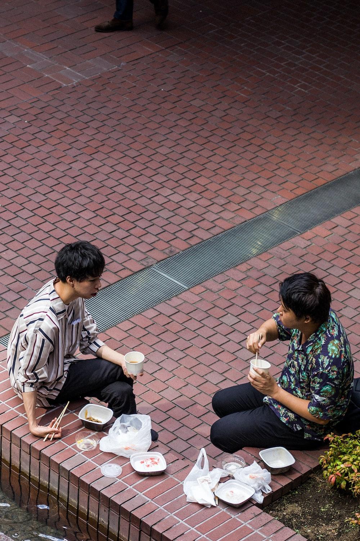 two men sitting on reddish brown concrete corner