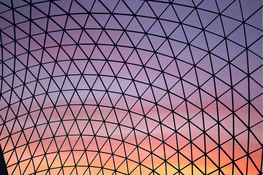 low-angle photography of clear glass dome building ceiling during golden hour