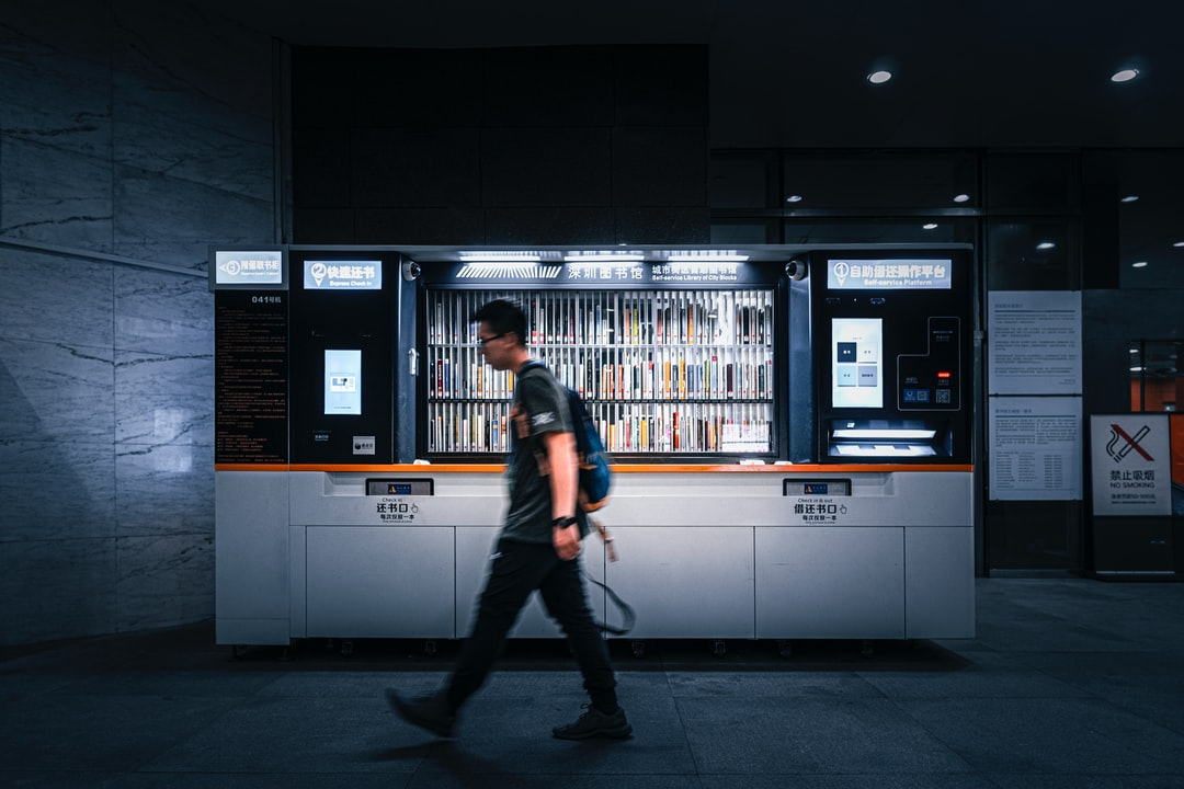 a young man passing by a self-service library machine. shot w/ my dear friend.