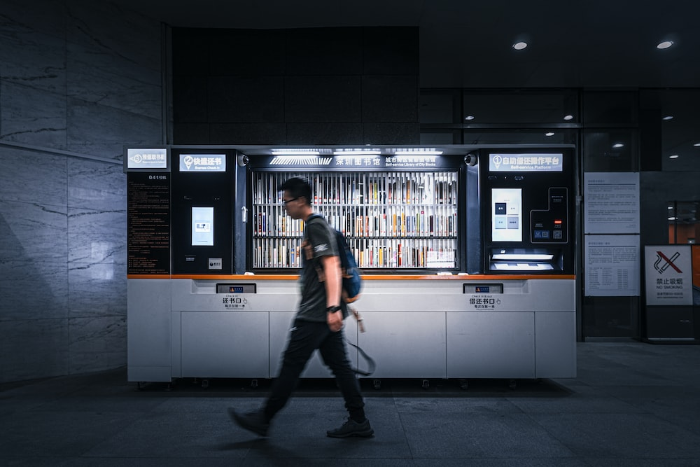 time-lapse photography of man passing by a storefront