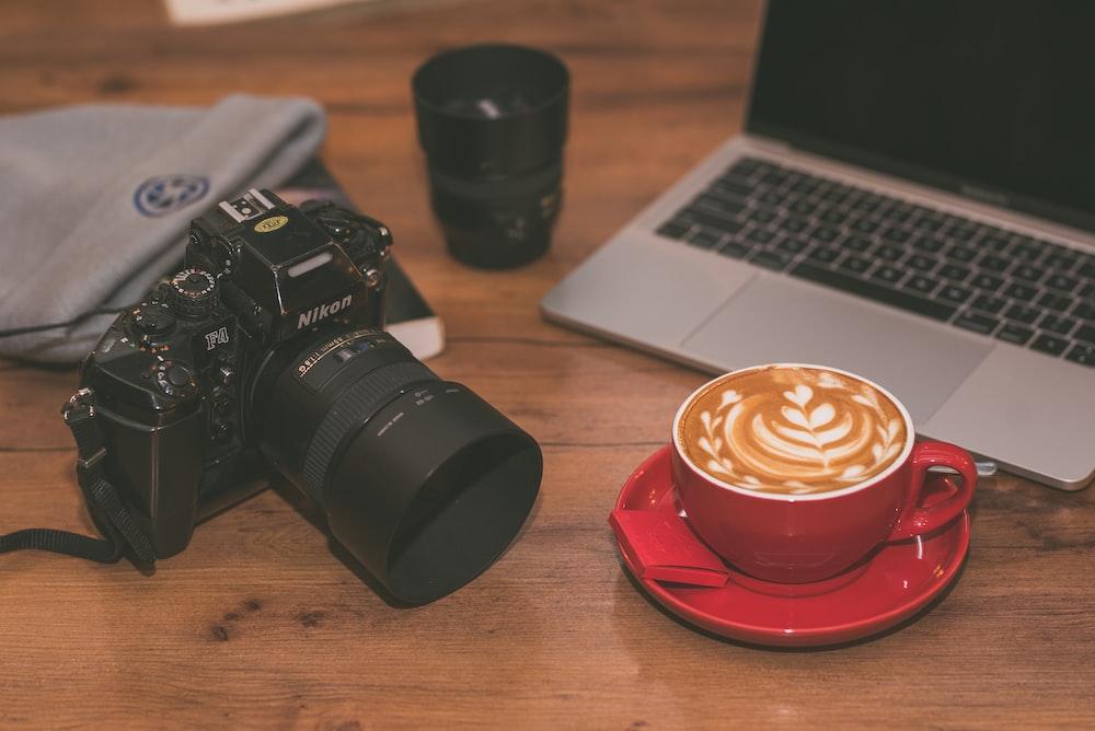 cappuccino in red ceramic mug near MacBook Pro, black camera lens, and black Nikon DSLR camera
