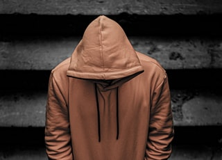 person in brown hoodie and black pants standing on staircase