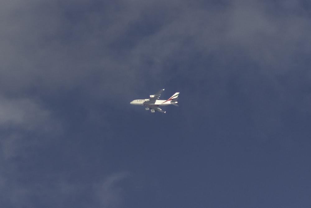 white airliner flying on sky