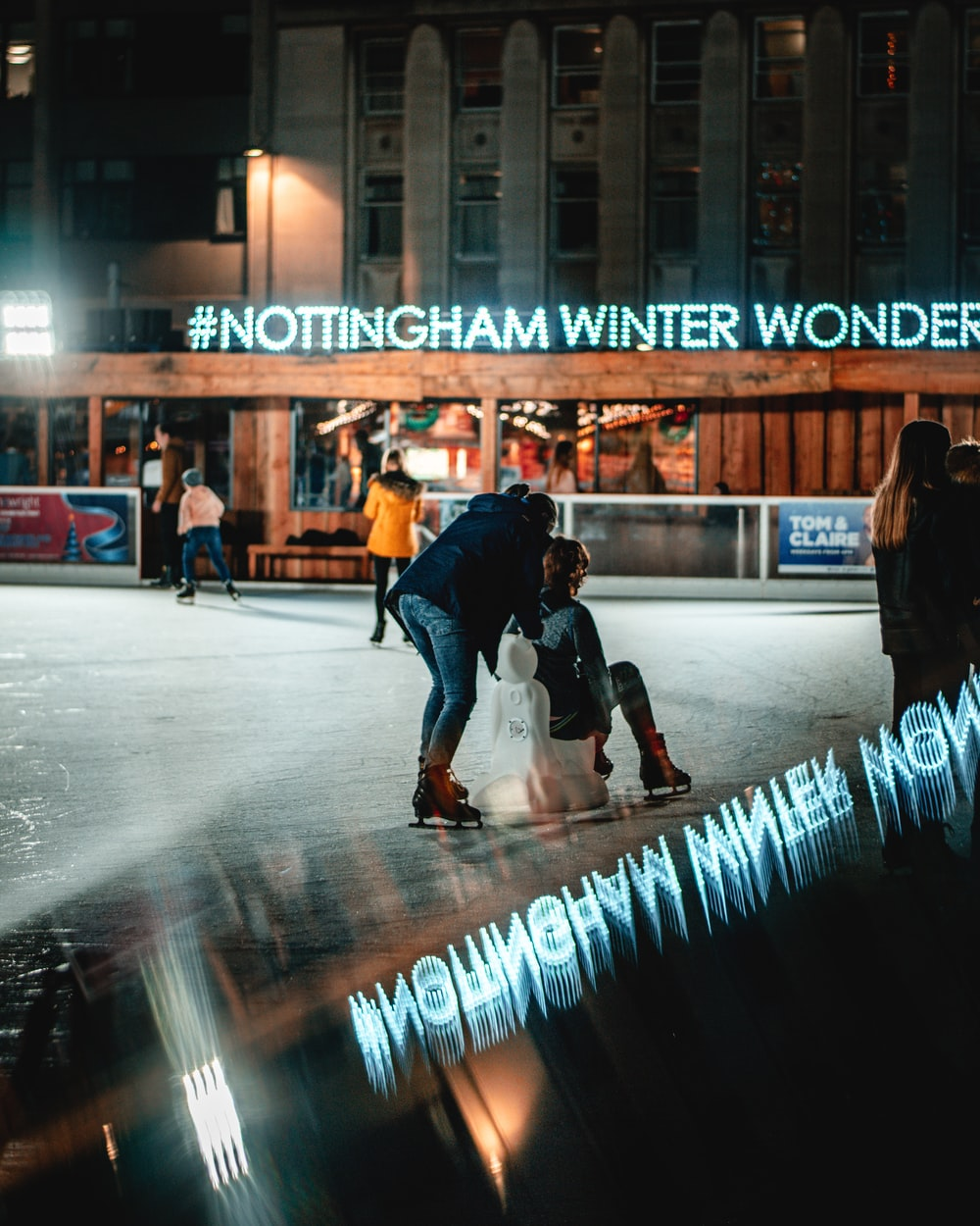 person sitting on white chair and another person standing viewing Nottingham Winter Wonderland building during night time