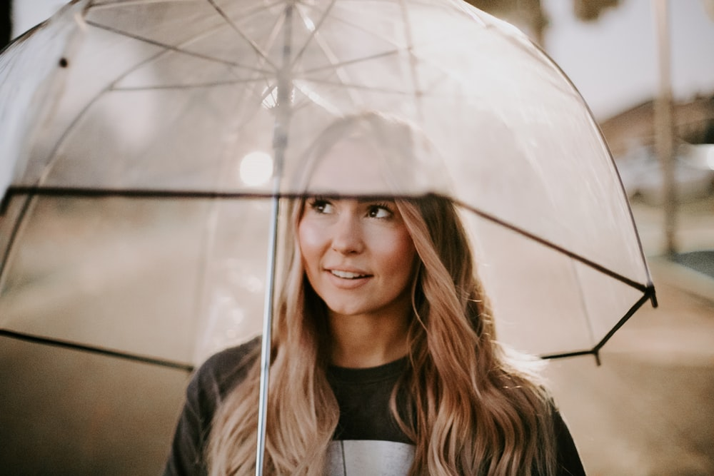 woman smiling and using clear umbrella during day