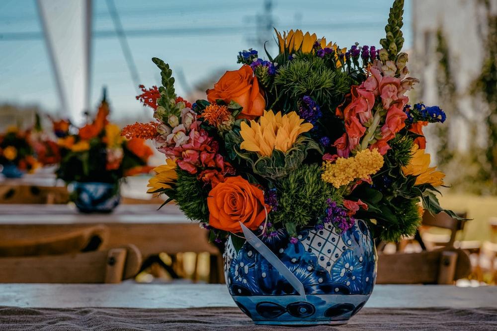 yellow, orange, and pink flower arrangement in blue floral vase