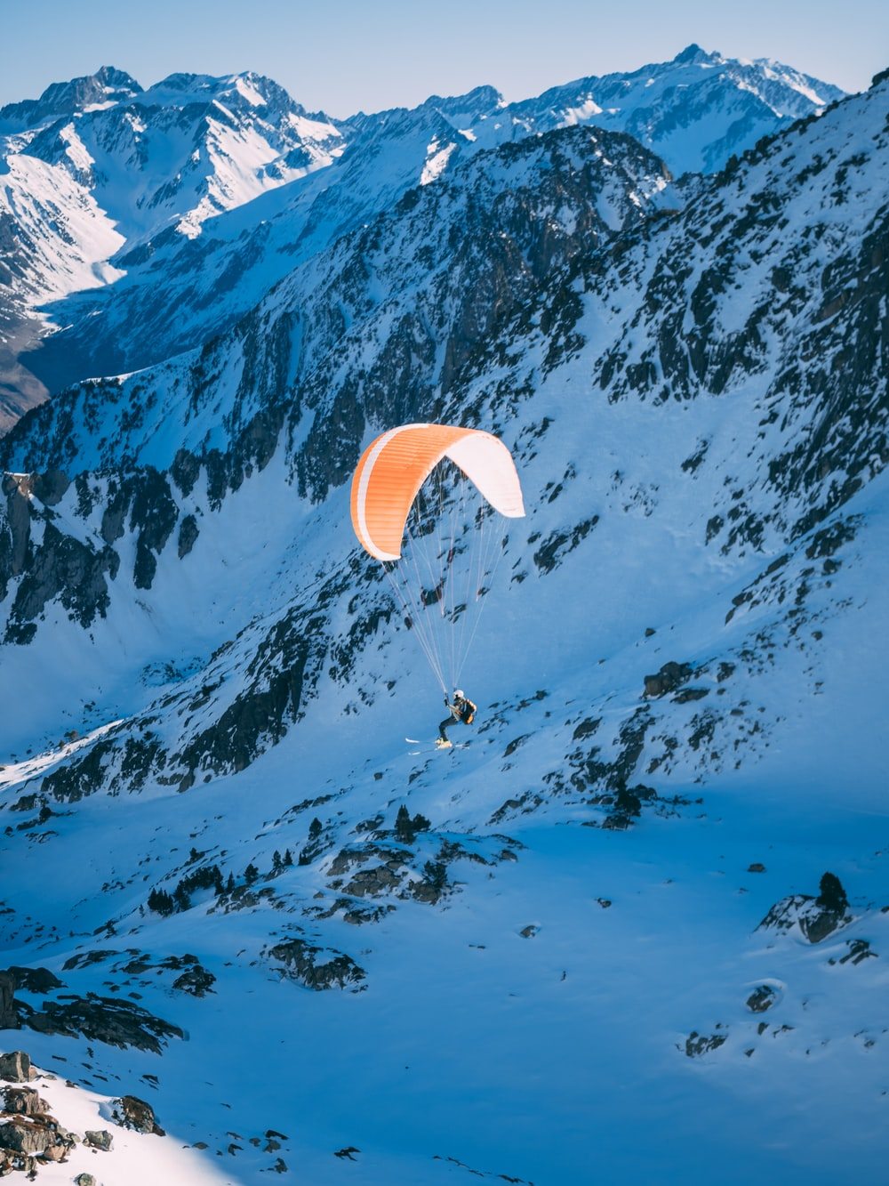 person riding parachute above glacier mountains and snowfield