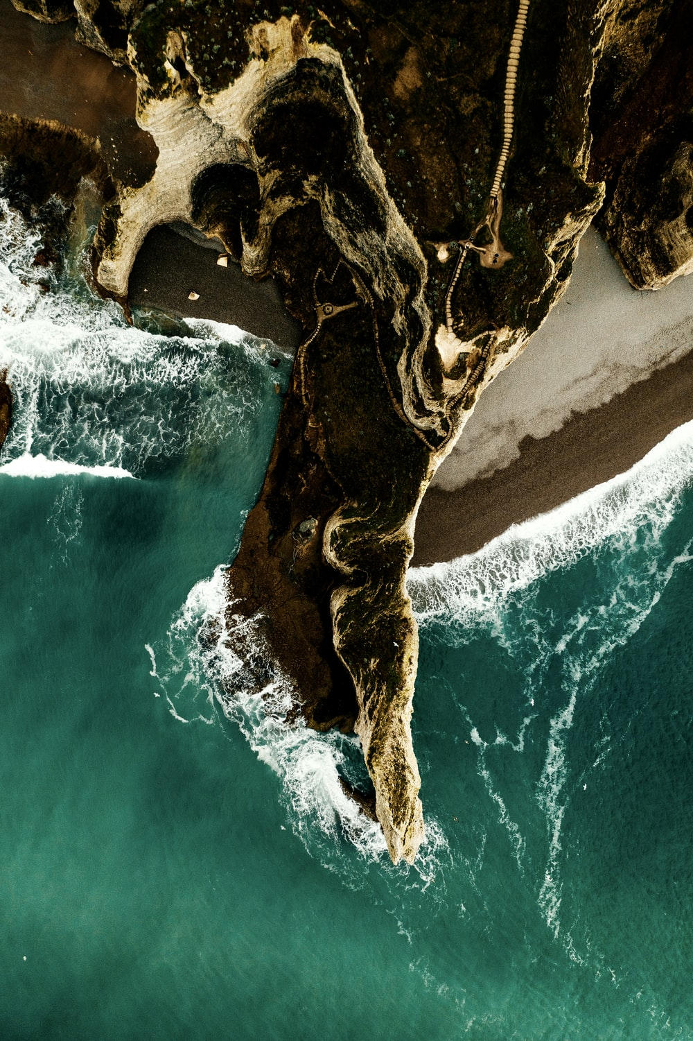 aerial photography of cliff viewing body of water during daytime