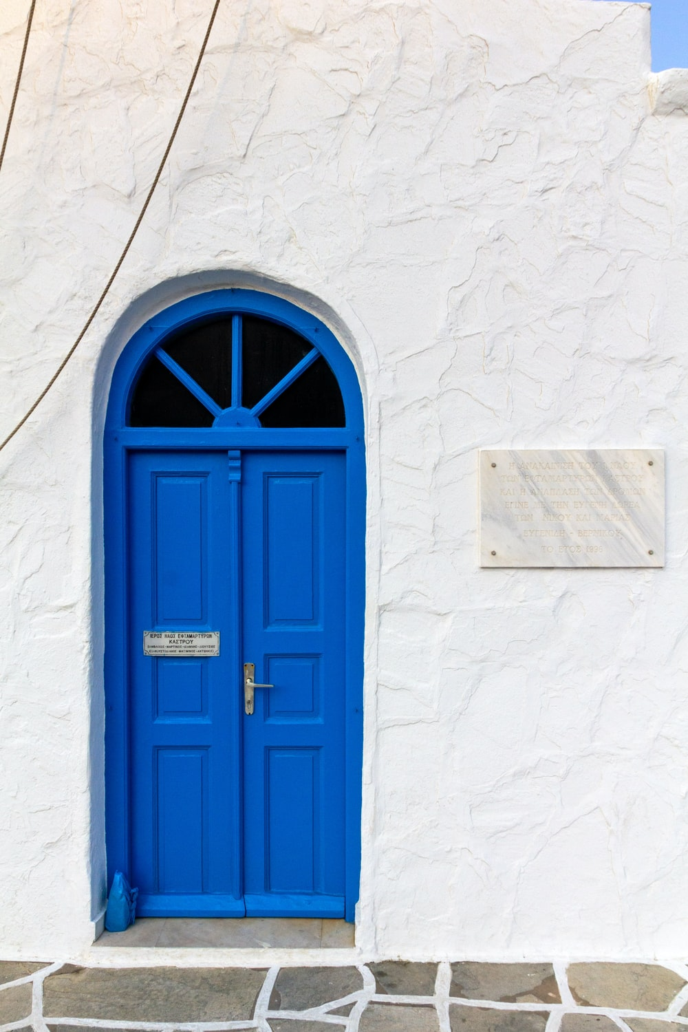 minimalist photography of a blue door in a white building