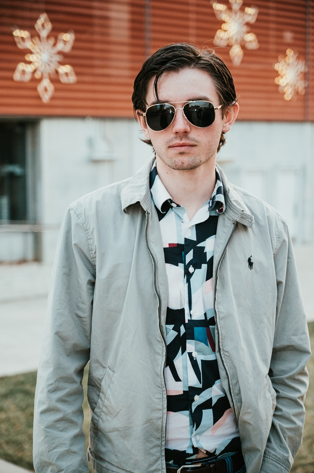 man wearing gray Ralph Lauren zip-up jacket and sunglasses standing