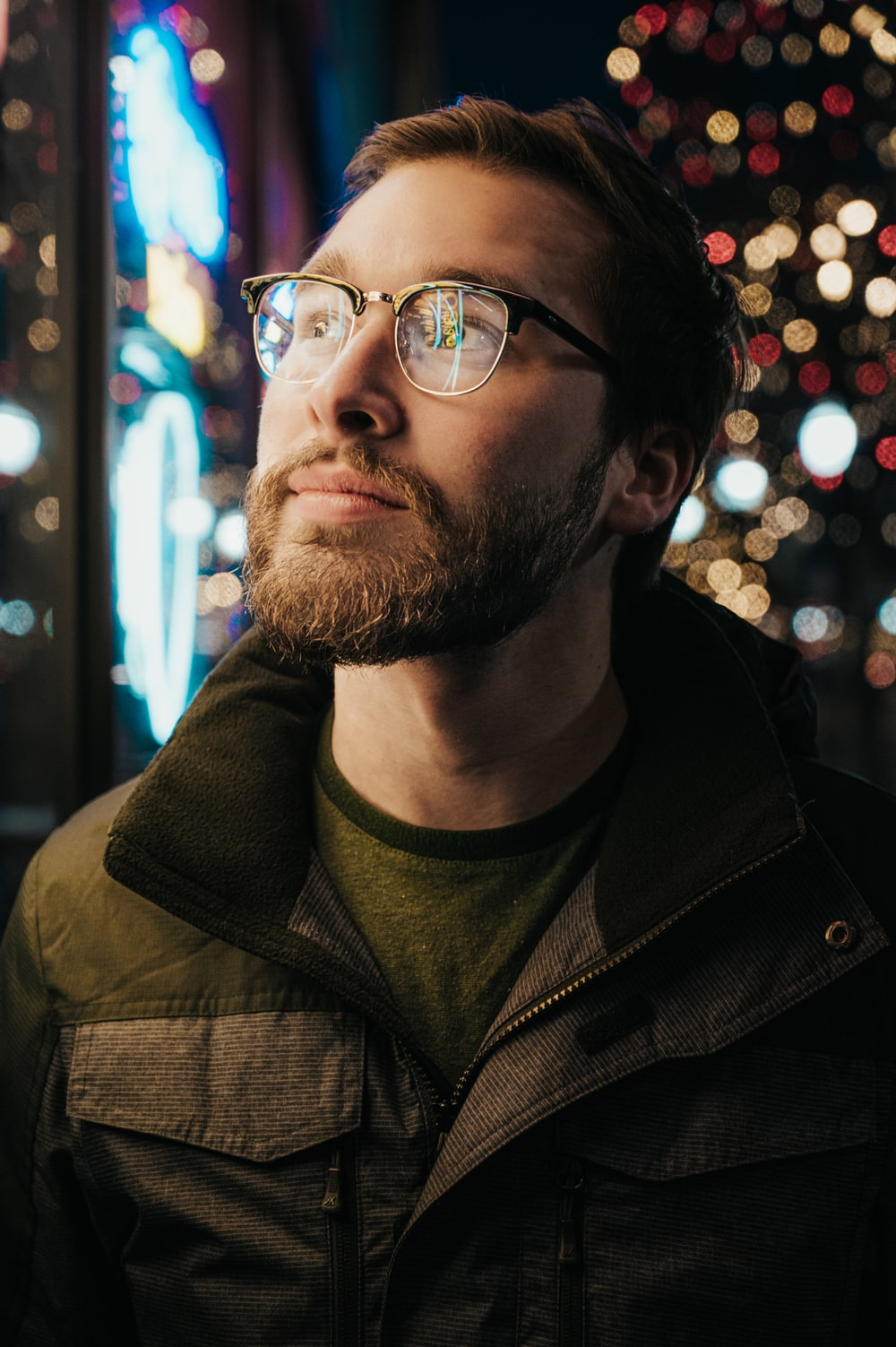 man in gray and green collared jacket wearing eyeglasses with turned-on lights
