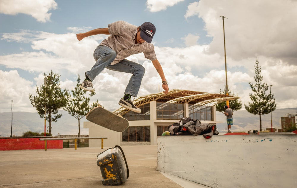 man riding skateboard in mid air above rock