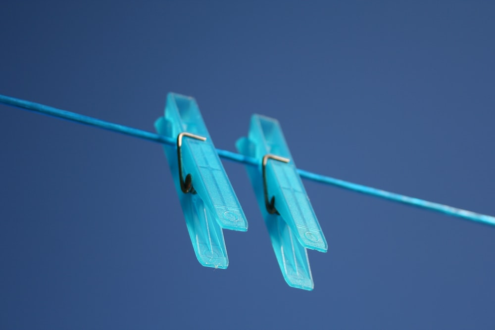 two blue plastic clothes pegs on a blue clothes line