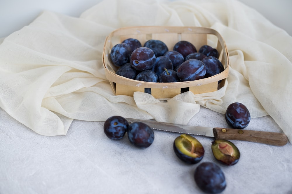 blueberry fruits in brown wicker basket near knife and white cloth
